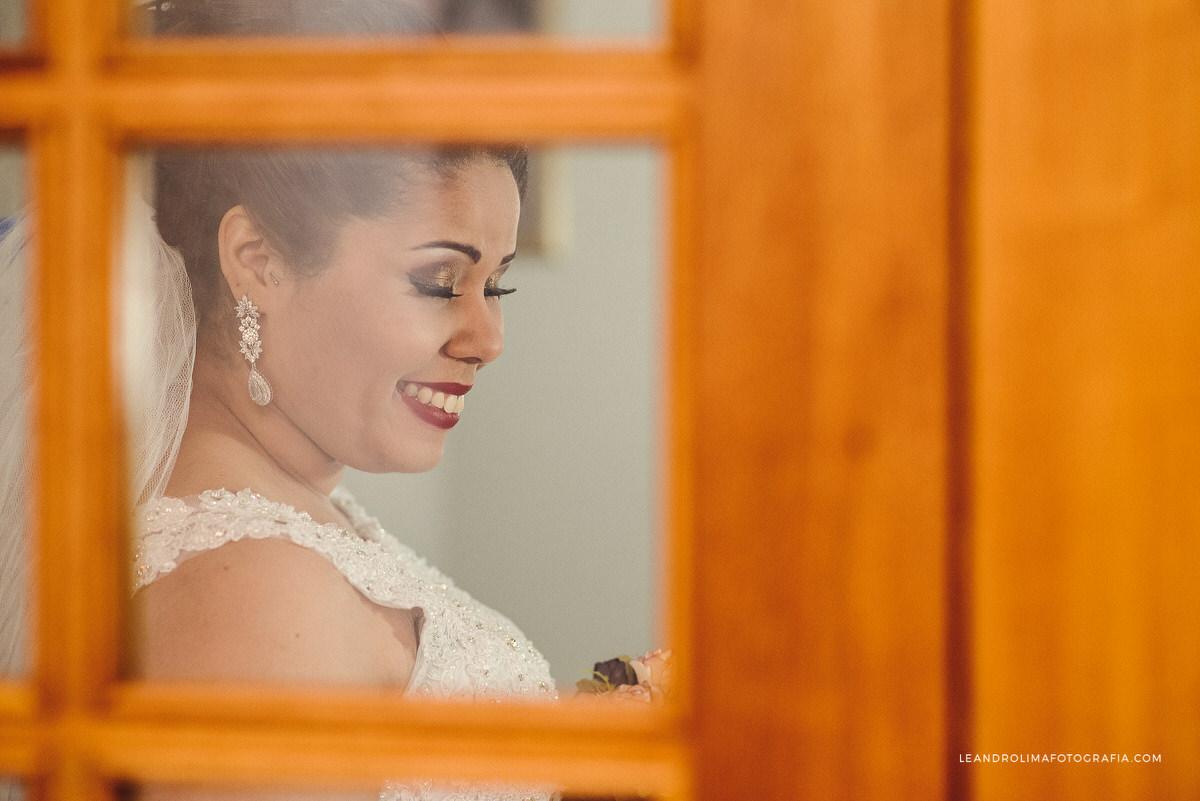 noiva-pronta-sorrindo-janela-vidro-moldura
